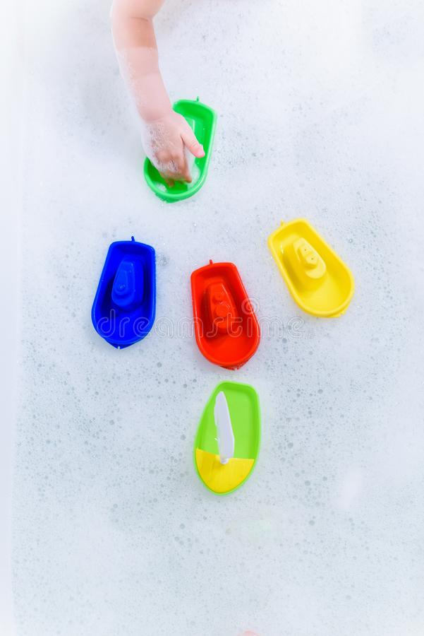 Crogioli multicolori di plastica di giocattolo sulla bagnoschiuma immagine stock libera da diritti