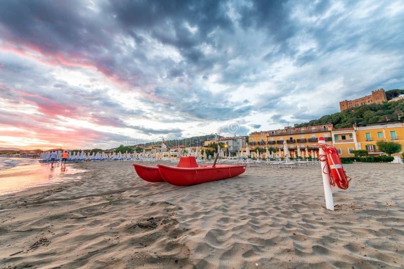 Crogiolo di pagaia rosso sulla spiaggia al tramonto immagine stock