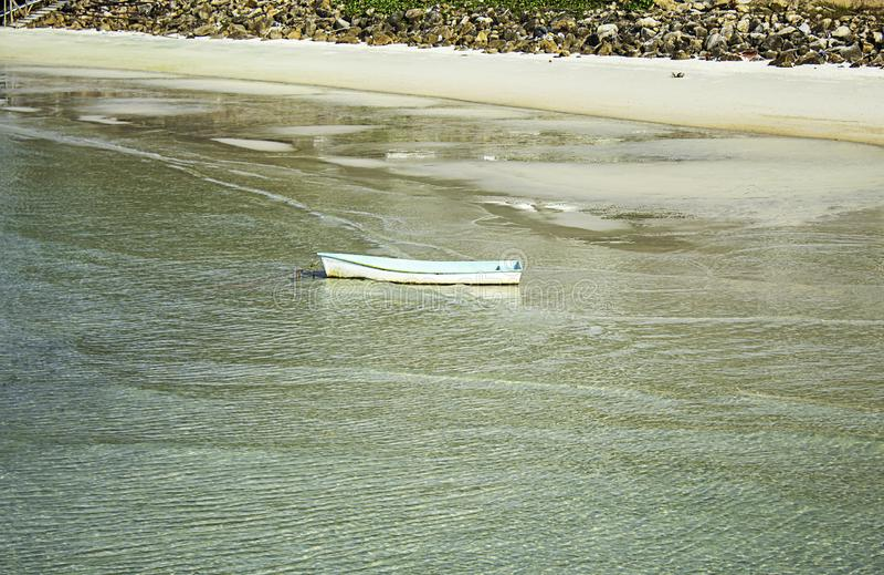 Crogiolo di vetroresina parcheggiato sulla spiaggia e sull'immondizia sulle rocce a Koh Phangan, Surat Thani in Tailandia fotografia stock