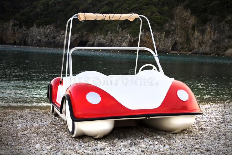 Crogiolo originale di acqua con pittura bianca e rossa È parcheggiato nella spiaggia sabbiosa e rocciosa È sistemato in un'isola  fotografia stock