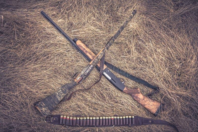 Croisé chassant des fusils de chasse avec la ceinture de munitions dans le rétro style de vintage sur l'herbe sèche comme fond de photos libres de droits
