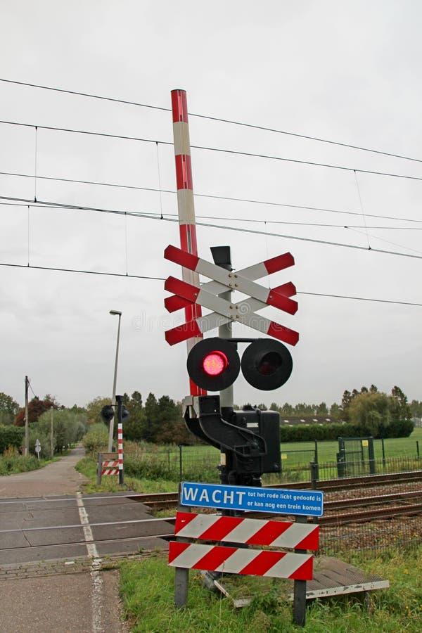 Croisement de chemin de fer avec la lumière rouge sur le signe et barrière dans le Zuidplaspolder près de Moordrecht photos stock