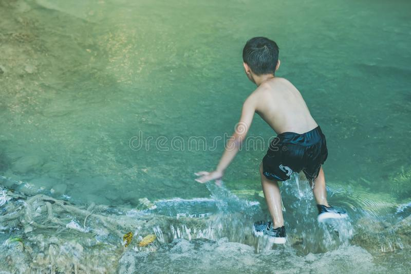 Croisement de petit garçon une rivière complètement des pierres soigneusement et chancelant en cascade au parc national d'Erawan photographie stock