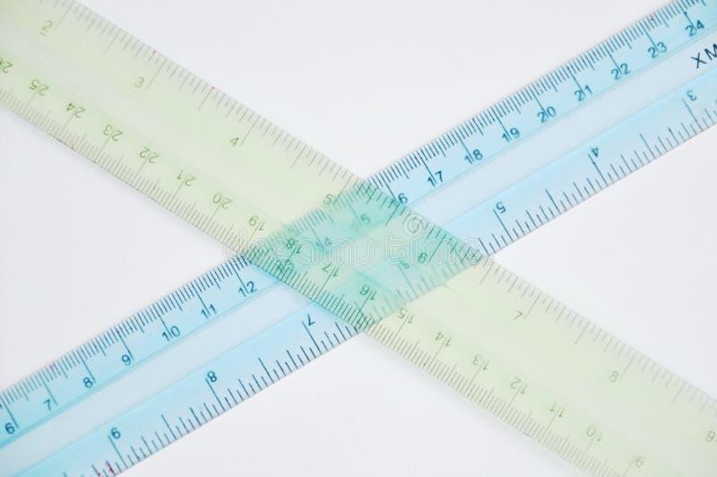 Croisement en plastique coloré de règle sur le fond blanc photographie stock