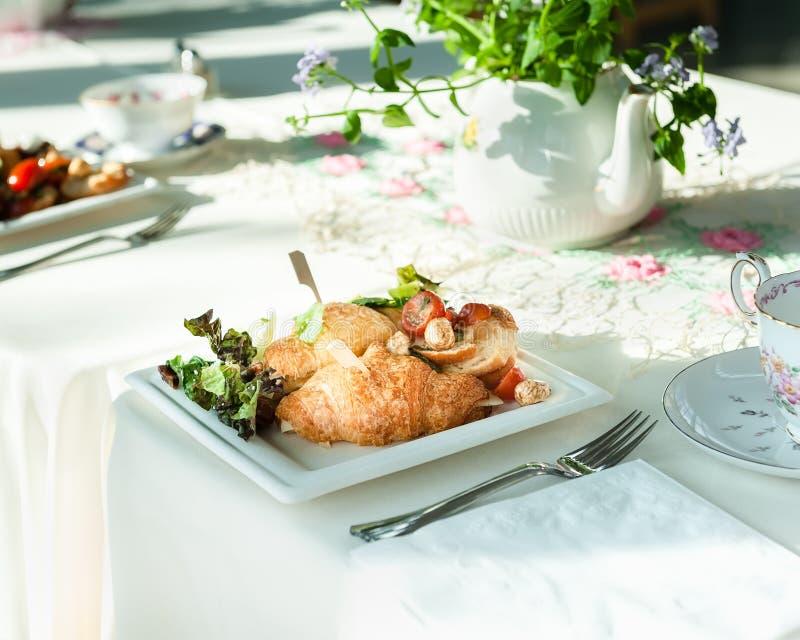 Croissant ściska na stole z teapot i filiżankami przy ślubnym lunchem obraz royalty free