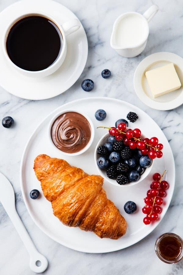 Croissant με τα φρέσκα μούρα, σοκολάτα που διαδίδονται και βούτυρο με το φλιτζάνι του καφέ σε ένα μαρμάρινο υπόβαθρο Τοπ όψη στοκ φωτογραφία με δικαίωμα ελεύθερης χρήσης