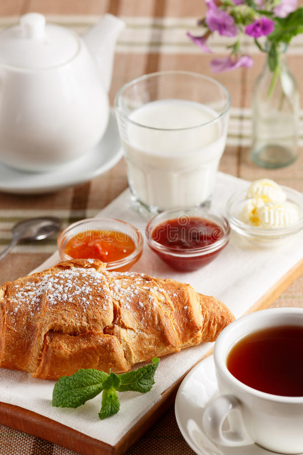 Croissant με τη μαρμελάδα, το βούτυρο και το τσάι στοκ εικόνες