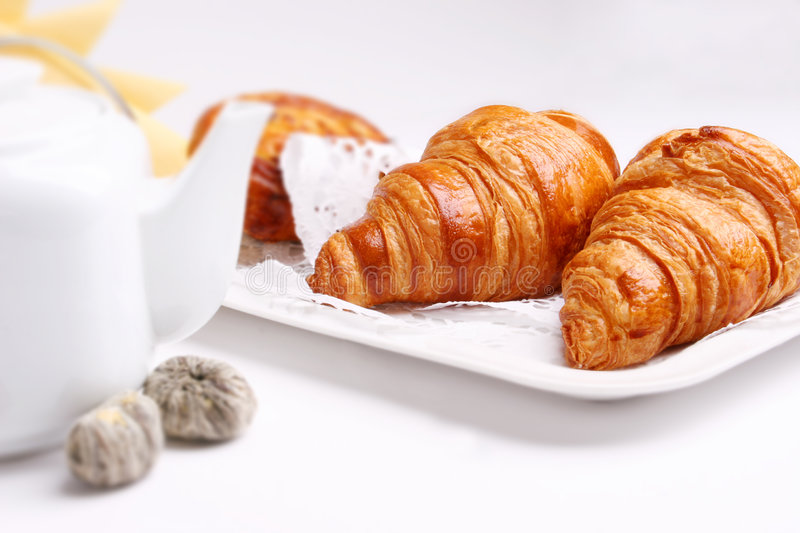 Croissant. Breakfast with croissant and a teapot royalty free stock image