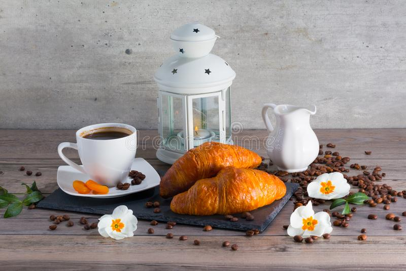 Croissant amanteigados franceses frescos para o café da manhã com o copo do café do aroma e da lâmpada do castiçal Bom começo par imagens de stock royalty free