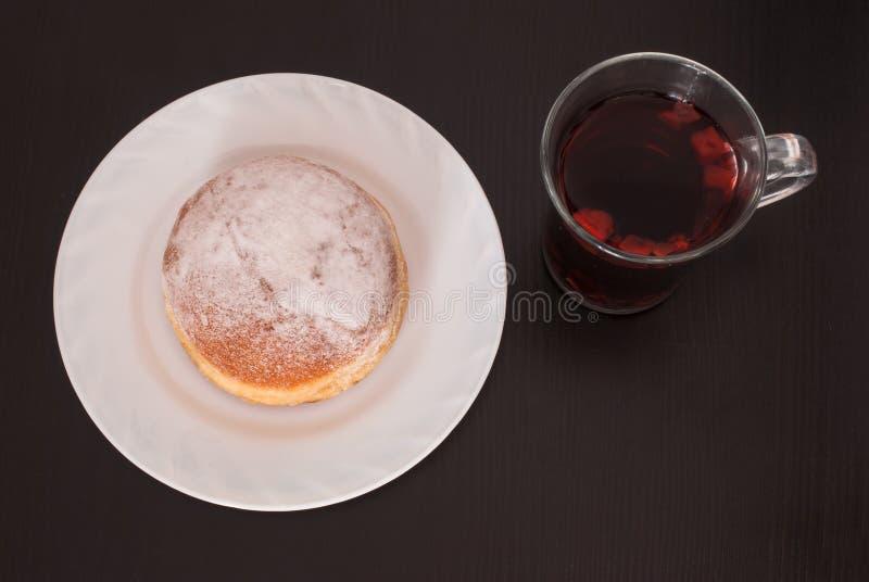 Croissant bávaro fresco e saboroso na placa branca e em um vidro do chá do fruto sobre o fundo de madeira imagens de stock royalty free