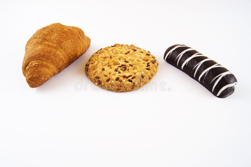 Croissant, biscuits with sesame seeds and nuts, cookies in chocolate on a light background royalty free stock images