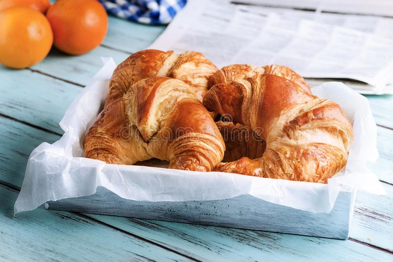Croissant, orange, newspaper for breakfast on wooden surface. Croissant and orange for breakfast on wooden surface stock photos