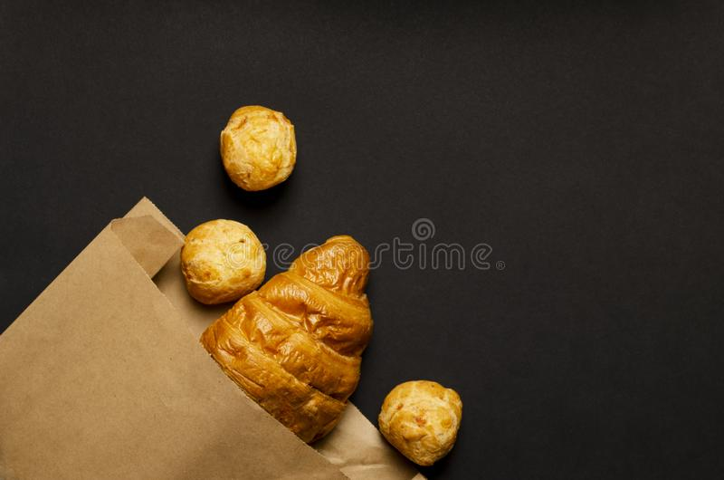 Croissant, cheese donuts in paper bag on black background. concept of continental breakfast and eco packaging stock images