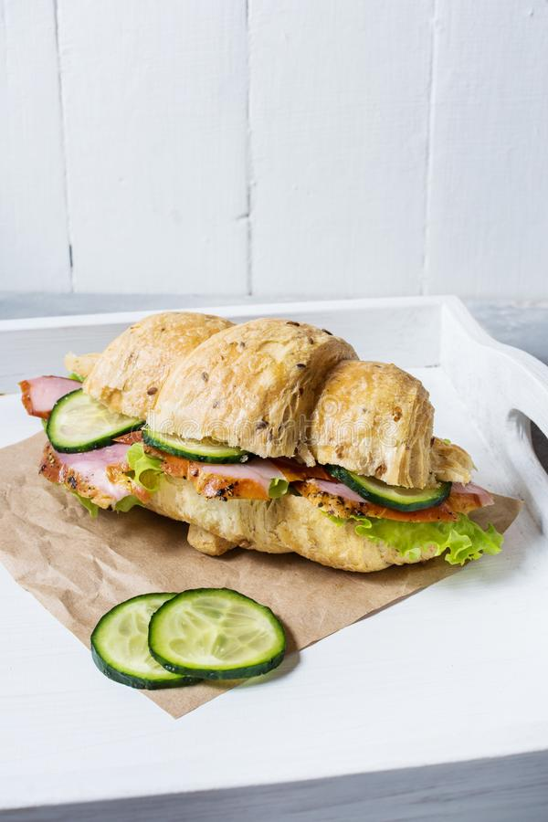 Croissant with cheese, ham, cucumber and salad on white tray royalty free stock photo