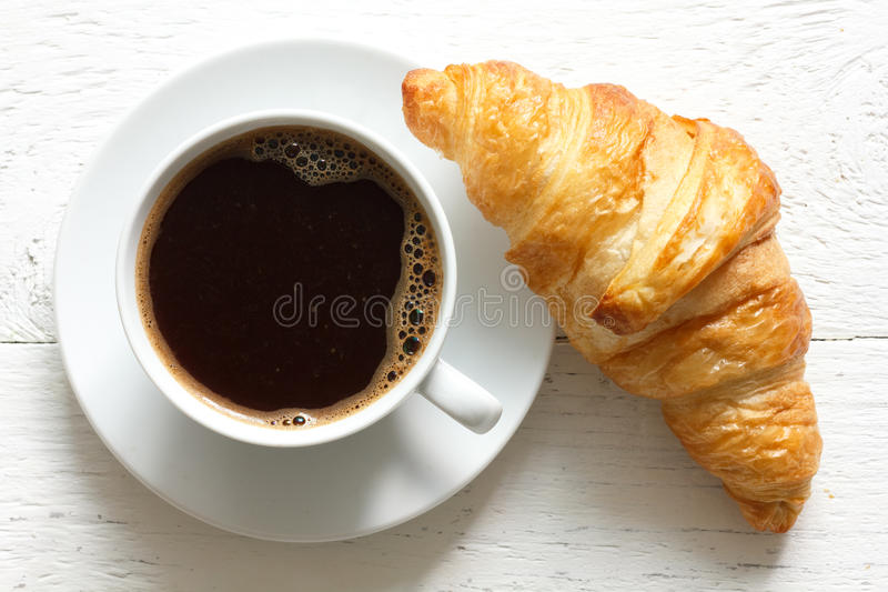Croissant and coffee on rustic white wood, from above. stock images