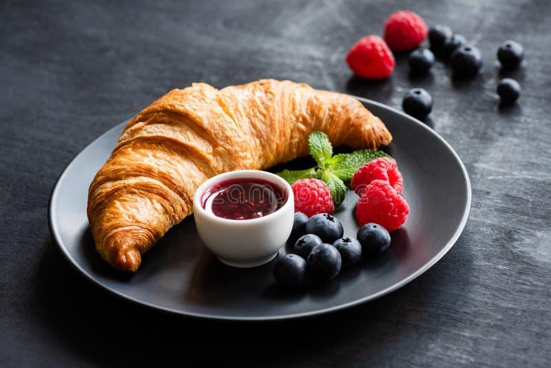 Croissant com bagas e doce frescos na placa preta foto de stock