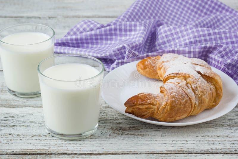 Croissant com leite na tabela de madeira velha para o fundo do café da manhã fotografia de stock