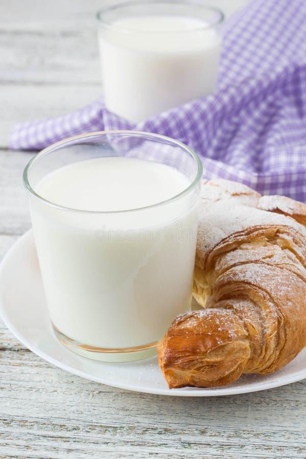 Croissant com leite na tabela de madeira velha para o fundo do café da manhã fotografia de stock royalty free