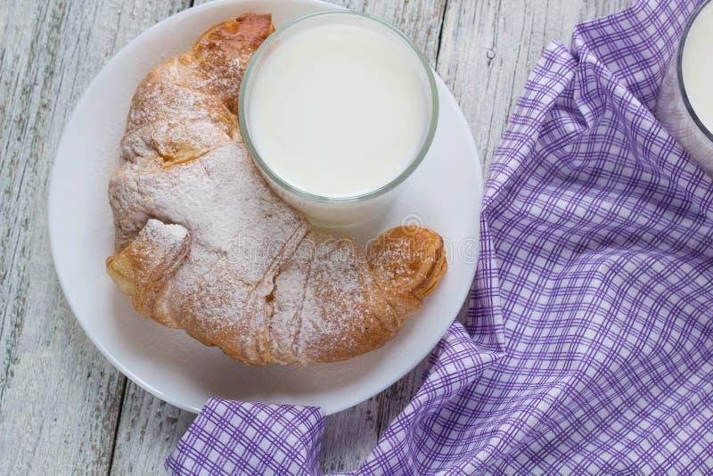 Croissant com leite na tabela de madeira velha para o fundo do café da manhã imagem de stock royalty free