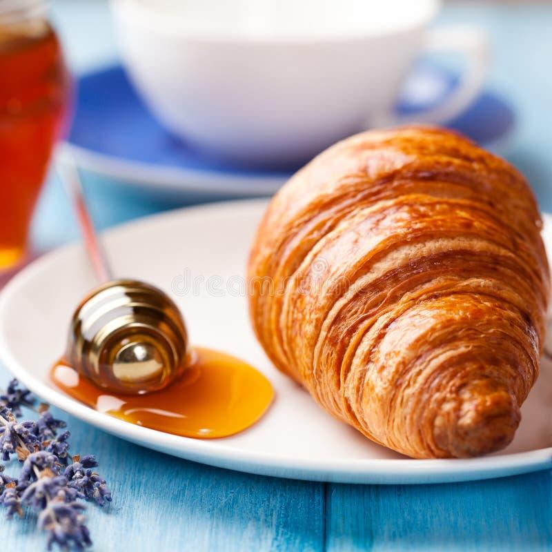Croissant com mel da alfazema fotografia de stock royalty free