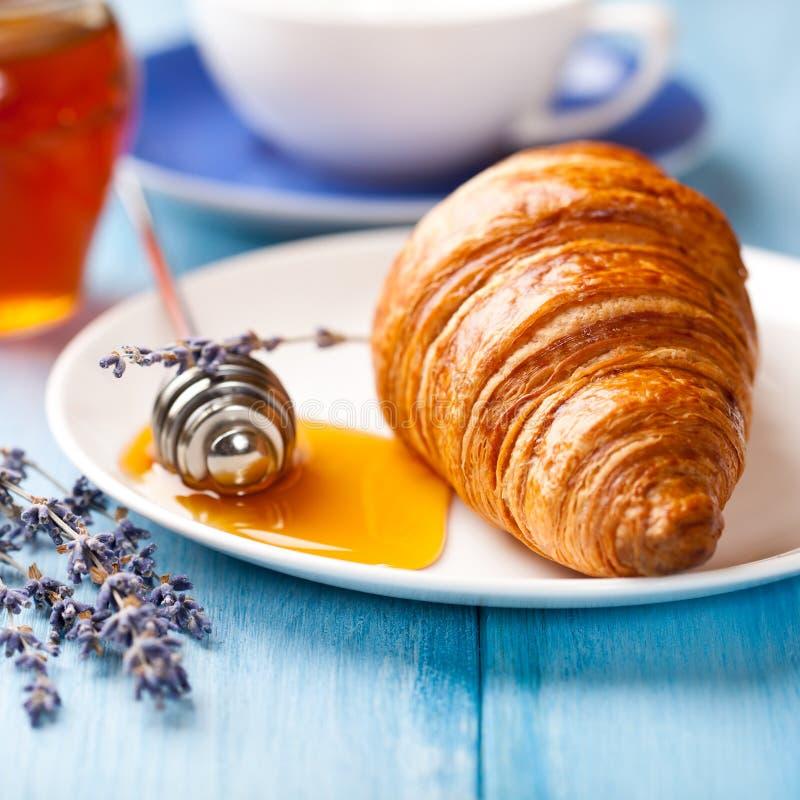 Croissant com mel da alfazema imagem de stock
