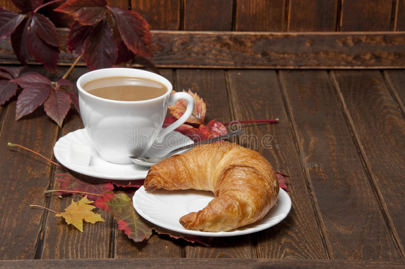 A croissant and a cup of coffeee with milk. On a old wooden table royalty free stock image