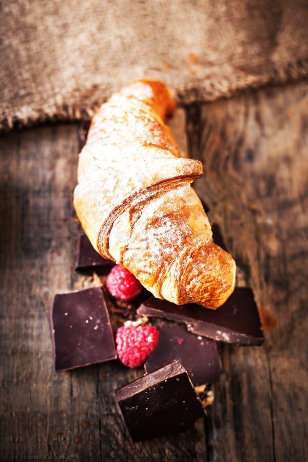 Croissant délicieux frais avec du chocolat et des framboises sur vieux image libre de droits