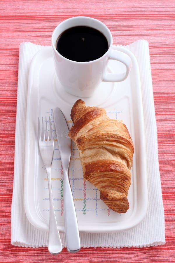 Croissant da manteiga e copo do café preto imagem de stock royalty free