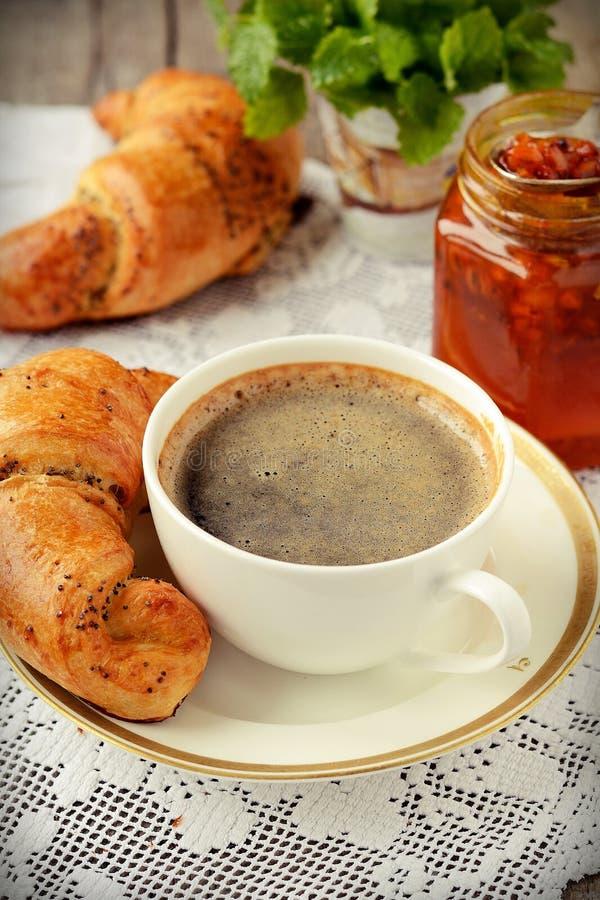 Croissant da semente de papoila com uma xícara de café imagem de stock royalty free
