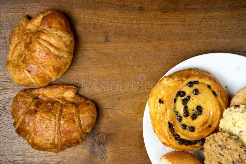 Croissant Deens en koekjesbakkerij op teak houten lijst stock afbeeldingen
