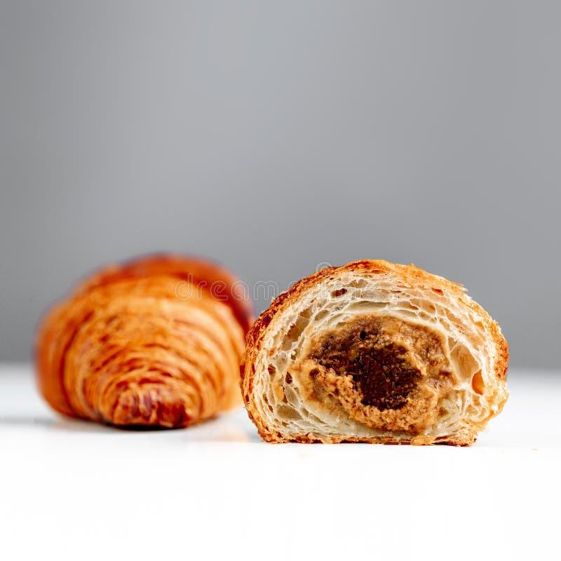 Croissant del cioccolato con le guarnizioni del caramello su fondo luminoso immagini stock libere da diritti