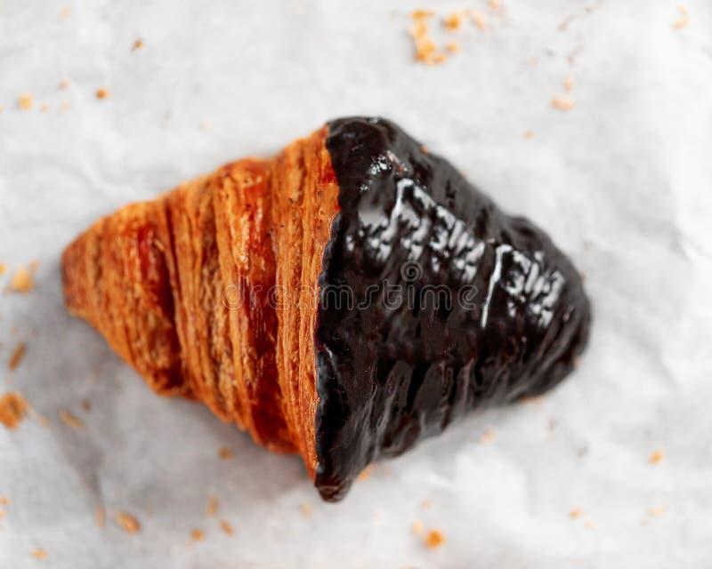Croissant del cioccolato su fondo luminoso, fine su immagine stock
