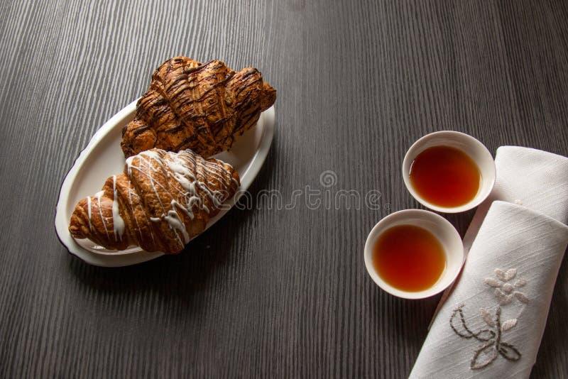 Croissant di recente al forno con cioccolato e zucchero in polvere su una tavola con il primo piano dei tovaglioli, vista superio fotografie stock