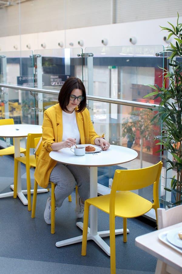 Croissant doux et une cuvette de caf? ? l'arri?re-plan Fille de brune dans une guêpe avec des verres, café potable à une table bl images stock