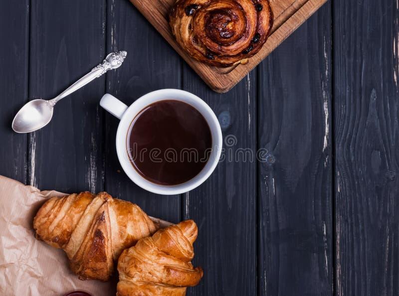 Croissant e café na tabela de madeira preta foto de stock royalty free