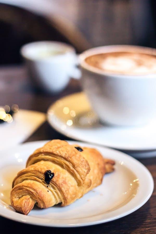 Croissant e caffè deliziosi Faccia colazione con la tazza di caffè ed i croissant al forno freschi su fondo di legno Stile d'anna fotografia stock libera da diritti