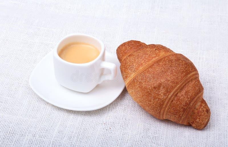 Croissant e caffè espresso freschi casalinghi croccanti su un fondo bianco, prima colazione di mattina, fuoco selettivo della taz immagine stock