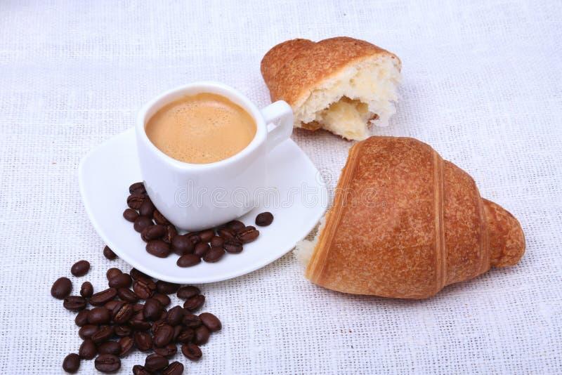 Croissant e caffè espresso freschi croccanti su un fondo bianco, prima colazione di mattina, fuoco selettivo della tazza di caffè fotografie stock libere da diritti