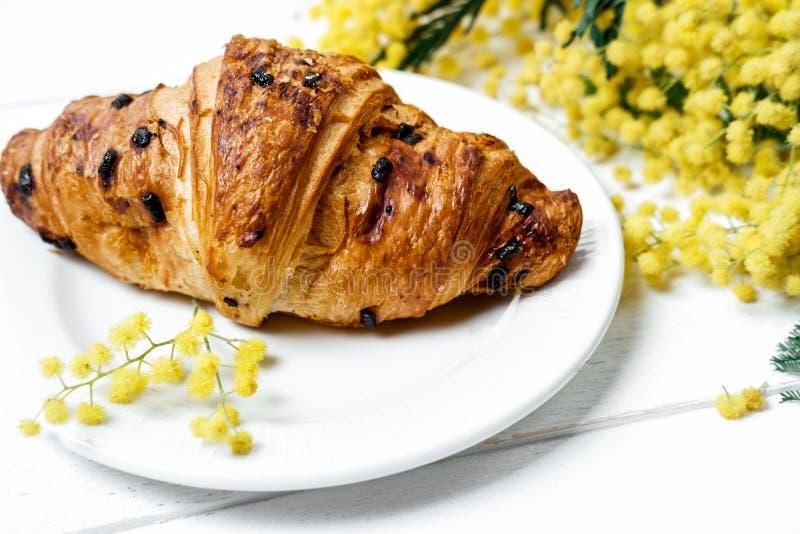 Croissant e cappuccino del cioccolato, decorati con il fiore della mimosa fotografie stock libere da diritti