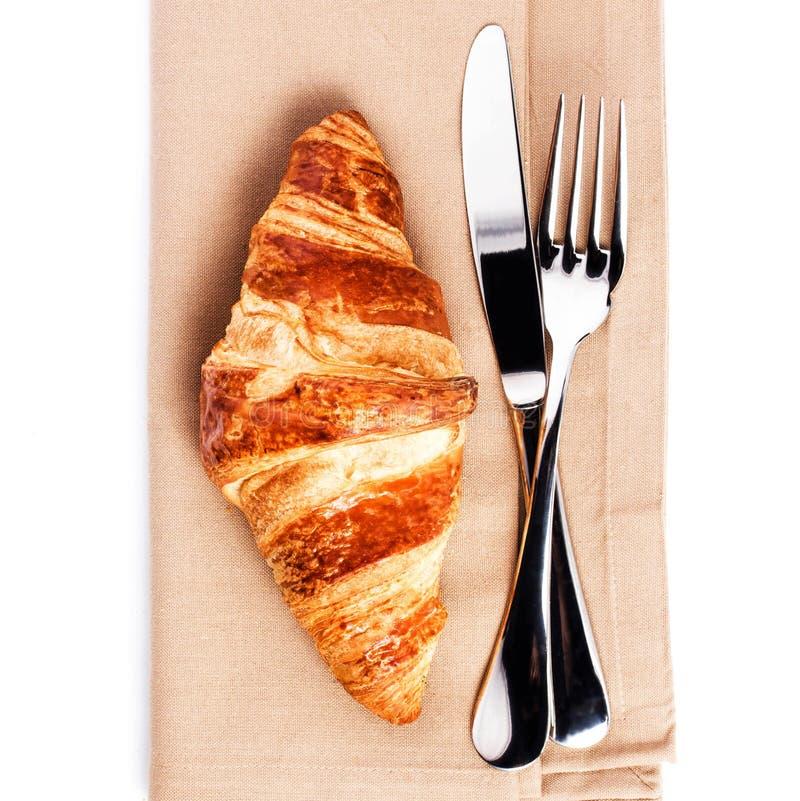 Croissant e cuttery frescos no guardanapo de linho isolado em b branco imagens de stock royalty free