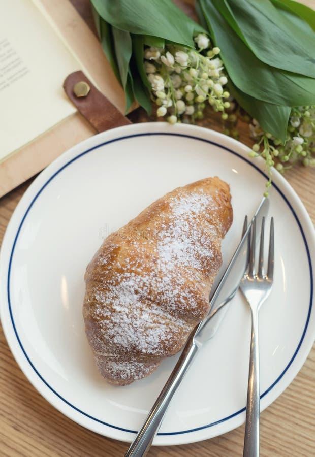 Croissant e flores como um fundo do café da manhã fotos de stock