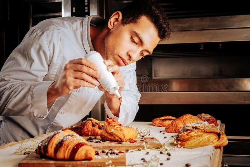 Croissant e sopros da cobertura do padeiro com doce de morango imagem de stock