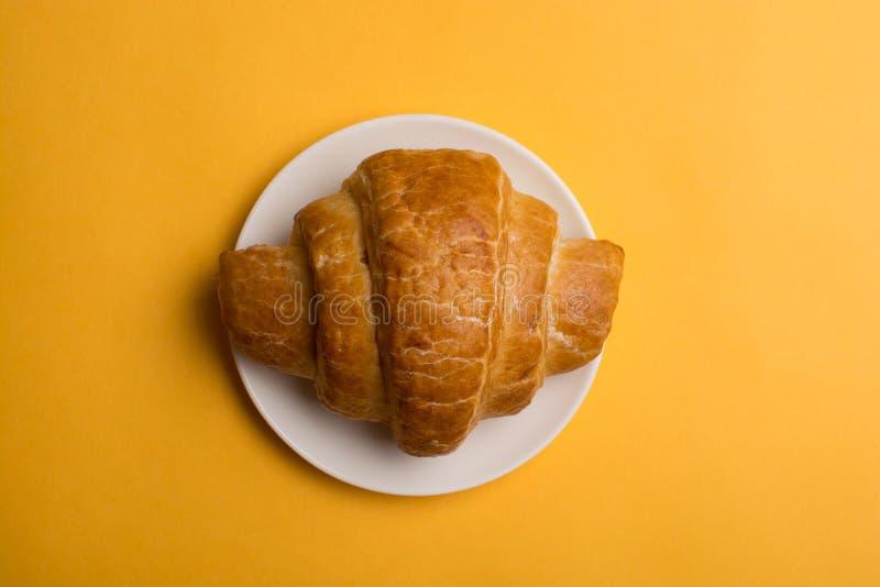 Croissant em uma placa branca em um fundo amarelo imagem de stock royalty free