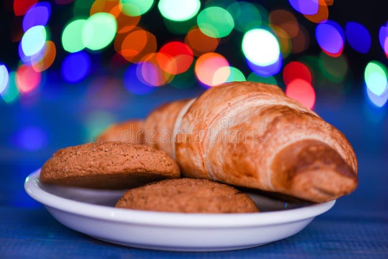 Croissant en haverkoekjes op witte plaat De traditie van de de wintervakantie Snoepjes voor Santa Claus en zijn helpers De kerstm stock foto