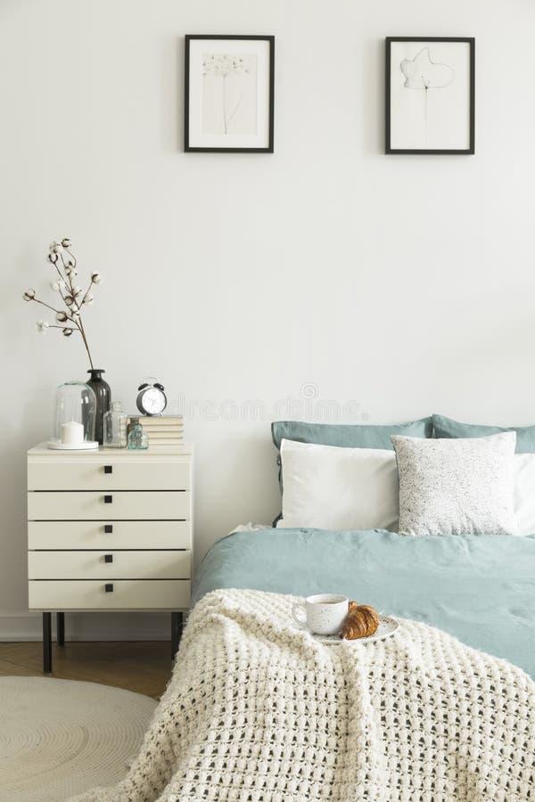 Croissant en koffie voor ontbijt op een deken op een bed in een binnenland van de pastelkleurslaapkamer Nightstand door het bed E stock afbeeldingen
