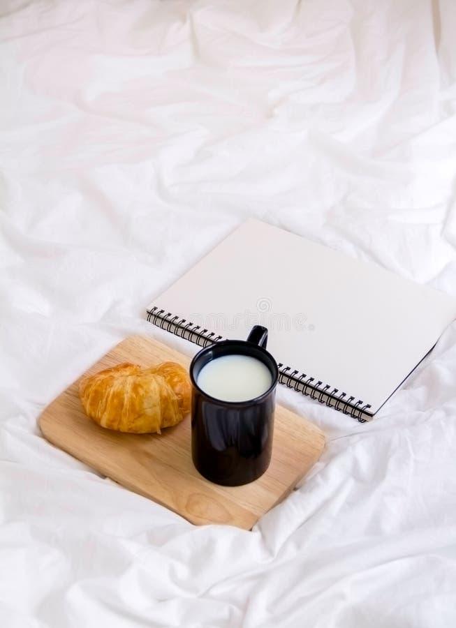 Croissant et livre sur la table de fonctionnement pendant le matin photos stock
