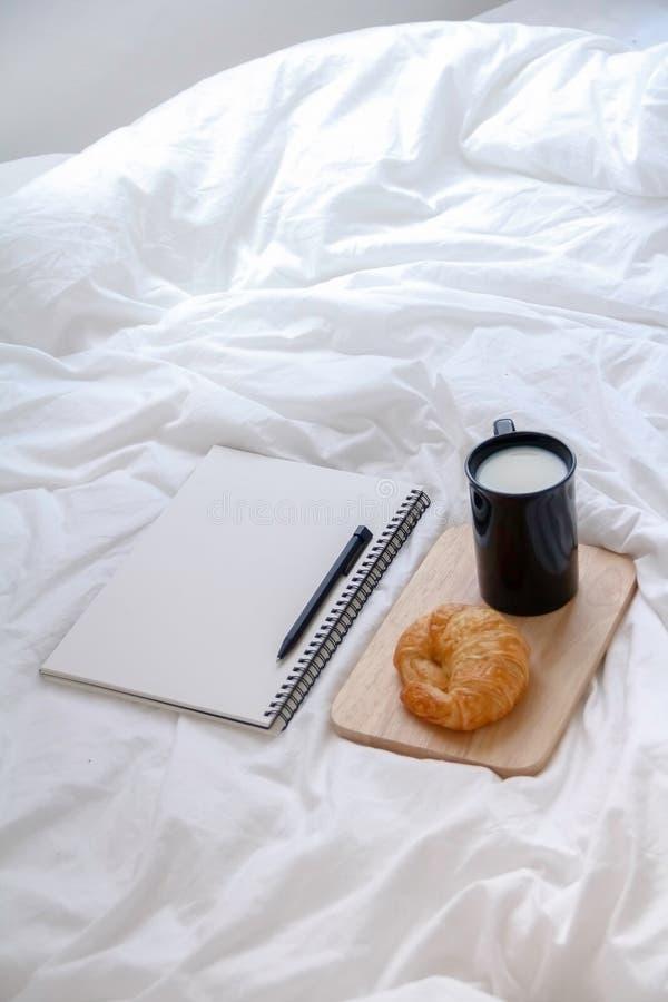 Croissant et livre sur la table de fonctionnement pendant le matin photos libres de droits