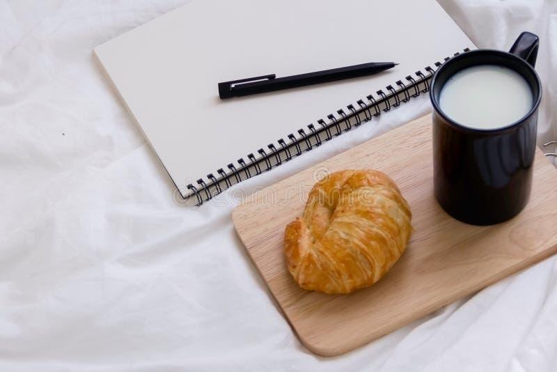 Croissant et livre sur la table de fonctionnement pendant le matin photographie stock