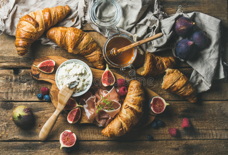 Croissant, formaggio di ricotta, fichi, bacche fresche, prosciutto di Parma e miele fotografia stock