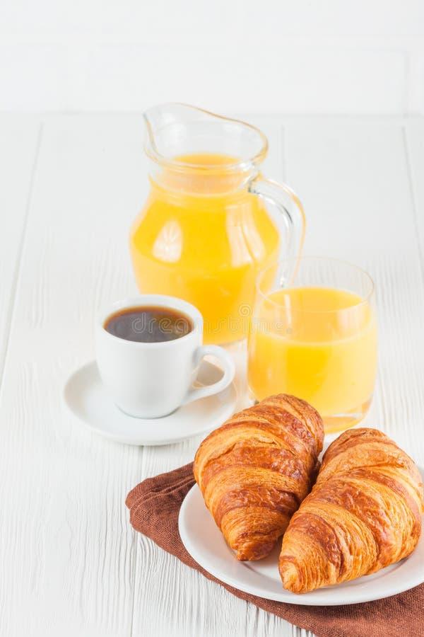 Croissant fraîchement cuit au four, jus d'orange, fruits frais, confiture sur le fond en bois blanc Pâtisseries fraîches de petit photos stock